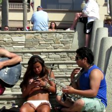 Tanned girl texts on her phone while music plays for her