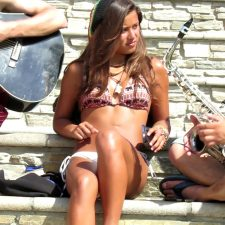 Hot girl in bikini talks to musician