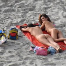 Blonde nudist girl talks to her friend on beach