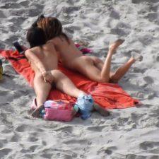 Naked brunette scratches her ass on beach