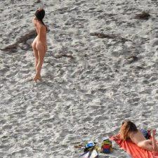 Elegant naked brunette poses on beach